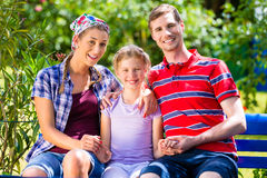 Family in garden sitting on bench Stock Photos