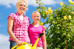 Family at gardening in front of rose bushes. Mother and daughter working in garden watering plants with can in front of rose bushes Stock Image