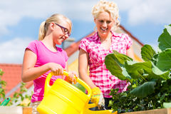 Family gardening in front of their home Royalty Free Stock Images