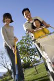 Family Gardening With Lawn Mower Stock Photo