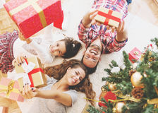 Family gather around a Christmas tree, holding presents Royalty Free Stock Image