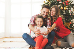 Family gathered around a Christmas tree, using a tablet stock images