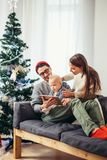 Family gathered around a Christmas tree, using a tablet. Christmas morning, cheerful family sitting in the living room having fun with the digital tablet that Royalty Free Stock Image