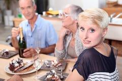 Family gathered around table Stock Photos