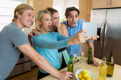Family gathered to watch a sports game on TV tablet streaming video excited and celebrating Royalty Free Stock Photo