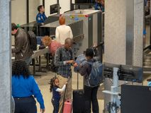 Family gathering belongings after passing through a Transportation Security Administration (TSA) checkpoint at JFK Airport. NEW YORK, NY – MAY 19, 2018 stock image