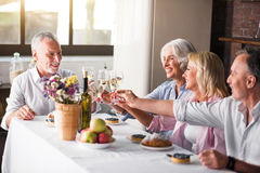 Family gathering for celebration in the kitchen. Cheering. Happy mature white family raising glassed at dinner table Royalty Free Stock Images