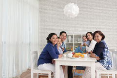 Family Gathering at Dinner Table. Traditional family values: portrait of big Asian family gathering at dinner table and looking at camera, smiling stock photography