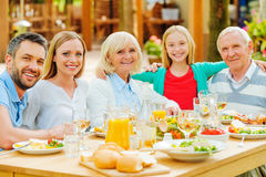 Family gathering. Happy family of five people bonding to each other and smiling while sitting at the dining table outdoors stock photos