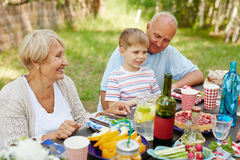 Family gathering. Little boy and his grandparents sitting by Thanksgiving table outdoors Stock Image