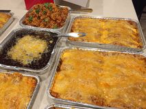 Family gathering meal. Homemade Enchiladas, rice and lasagne Stock Photos