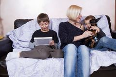 Family gathering. Mother playing with a dog with one son and other son playing with a tablet royalty free stock photo
