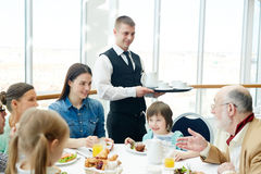 Family gathering. Family of six having meals in restaurant with waiter near by royalty free stock photos