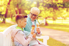 Old man and boy eating ice cream at summer park. Family, generation, communication and people concept - happy grandfather and grandson eating ice cream at summer Stock Photo