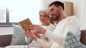 Adult son and senior mother with photo at home. Family, generation and people concept - happy smiling adult son and senior mother looking at photo at home stock video