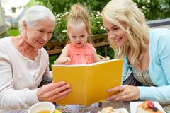 Happy family reading book at cafe terrace Royalty Free Stock Photos