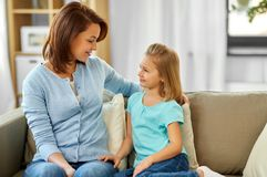 Mother and daughter looking at each other at home stock photography