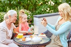 Woman photographing her family at cafe. Family, generation and people concept - happy smiling mother with smartphone photographing daughter and grandmother at Royalty Free Stock Photography