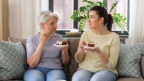 Old mother and adult daughter eating cake at home