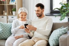 Old mother and adult son with smartphone at home royalty free stock images