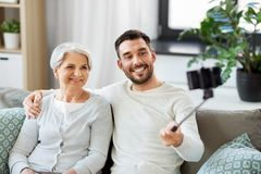 Senior mother with adult son taking selfie at home stock photography