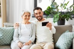 Senior mother with adult son taking selfie at home royalty free stock image