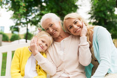 Woman with daughter and senior mother at park. Family, generation and people concept - happy smiling women with daughter and senior mother sitting on park bench Stock Photos