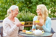Daughter with senior mother drinking tea at cafe. Family, generation and people concept - happy smiling young daughter with senior mother drinking tea at cafe or Stock Image