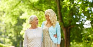 Daughter with senior mother hugging at park stock photo