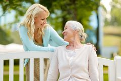Daughter with senior mother hugging on park bench. Family, generation and people concept - happy smiling young daughter with senior mother sitting on park bench Stock Image