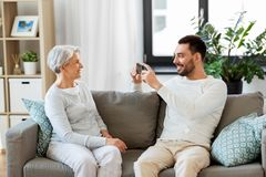 Adult son photographing senior mother at home stock photography