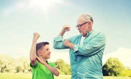 Happy grandfather and grandson showing muscles royalty free stock photos