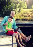 Grandfather and boy with tablet pc on river berth stock images