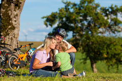Family on getaway with bikes. Happy family (father, mother and son) on getaway with bikes - they have a break stock images