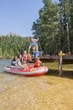 Family Getting Into Inflatable Boat For Fishing Trip Stock Photo