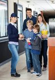 Family Getting Tickets Checked By Worker At Cinema Royalty Free Stock Images
