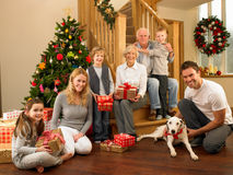 Family with gifts in front of Christmas tree. Smiling at camera stock photos
