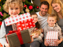 Family with gifts in front of Christmas tree. Smiling at camera stock photography