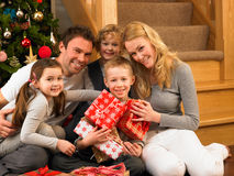 Family with gifts in front of Christmas tree. Smiling at camera Royalty Free Stock Photos