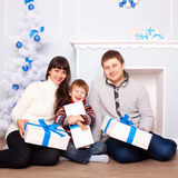 Family with gifts near Christmas tree. Royalty Free Stock Image