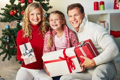 Family with gifts. Portrait of happy family with giftboxes looking at camera on Christmas day Royalty Free Stock Photo
