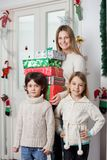 Family With Gifts Standing By Door During Royalty Free Stock Images