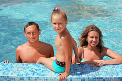 Family with girl bathe in pool, daughter sits near Stock Images
