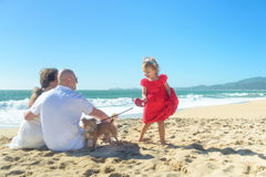 Family with girl in red dress and dog on the beach Stock Image