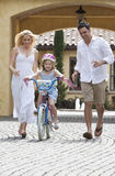 Family WIth Girl Riding Bike & Happy Parents Stock Photos
