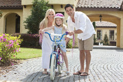 Family WIth Girl Riding Bike & Happy Parents Royalty Free Stock Photography