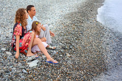 Family with girl sitting on beach, Looking afar Royalty Free Stock Photo