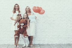 Family with Girl in White Dress Holding Toy Bear. Gift Box. Young Woman. Blonde Hair. Standing Woman. Celebration Concept. Holiday in March. Plush Toy. Red stock photos