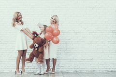 Family with Girl in White Dress Holding Toy Bear. Gift Box. Young Woman. Blonde Hair. Standing Woman. Celebration Concept. Holiday in March. Plush Toy. Red stock image