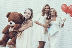 Family with Girl in White Dress Holding Toy Bear. Gift Box. Young Woman. Blonde Hair. Standing Woman. Celebration Concept. Holiday in March. Plush Toy. Red royalty free stock photography